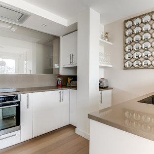 Réalisation d'une cuisine ouverte parallèle design de taille moyenne avec un évier encastré, des portes de placard blanches, une crédence beige, un électroménager encastrable, un sol en bois brun et aucun îlot.