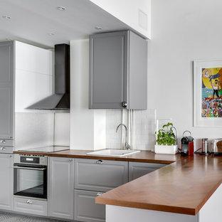 Idée de décoration pour une cuisine méditerranéenne en L avec un évier posé, un placard avec porte à panneau surélevé, des portes de placard grises, un plan de travail en bois, une crédence blanche, une crédence en carrelage métro, un électroménager en acier inoxydable, une péninsule, un sol gris et un plan de travail marron.