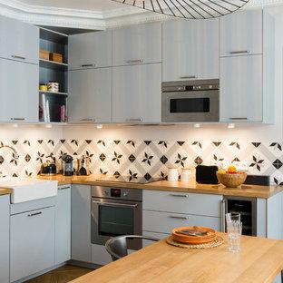Idée de décoration pour une cuisine américaine design en L de taille moyenne avec un placard à porte plane et des portes de placard grises.