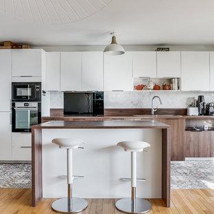 Aménagement d'une grande cuisine américaine linéaire avec des portes de placard blanches, un plan de travail en bois, un électroménager en acier inoxydable, un îlot central, un plan de travail marron, une crédence blanche, une crédence en mosaïque et un sol en carreaux de ciment.