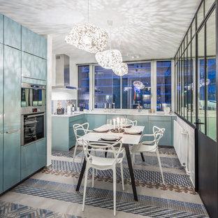 Idée de décoration pour une cuisine design en L fermée avec des portes de placard bleues, une crédence multicolore et un électroménager en acier inoxydable.