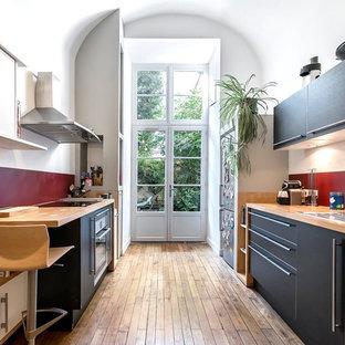 Exemple d'une grand cuisine parallèle tendance fermée avec un évier posé, un placard à porte plane, des portes de placard noires, un plan de travail en bois, une crédence rouge, un sol en bois brun, aucun îlot et un électroménager en acier inoxydable.