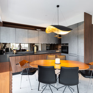 Photo of a large midcentury u-shaped eat-in kitchen in Nice with an integrated sink, beaded inset cabinets, medium wood cabinets, quartzite benchtops, brown splashback, timber splashback, black appliances, marble floors, no island, grey floor and black benchtop.