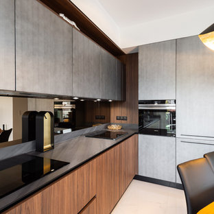Large midcentury u-shaped eat-in kitchen in Nice with an integrated sink, beaded inset cabinets, medium wood cabinets, quartzite benchtops, brown splashback, timber splashback, black appliances, marble floors, no island, grey floor and black benchtop.