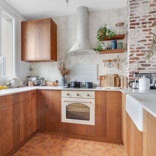 パリの中くらいの北欧スタイルのおしゃれなコの字型キッチン (珪岩カウンター、グレーのキッチンパネル、テラコッタタイルの床、オレンジの床、白いキッチンカウンター、フラットパネル扉のキャビネット、中間色木目調キャビネット、アイランドなし、エプロンフロントシンク、白い調理設備) の写真