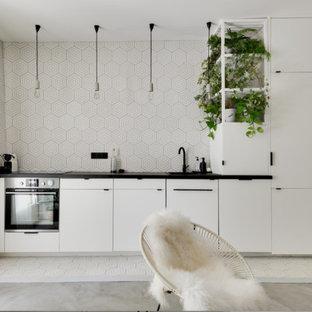 Aménagement d'une cuisine ouverte linéaire scandinave avec un évier 1 bac, un placard à porte plane, des portes de placard blanches, une crédence multicolore, un électroménager en acier inoxydable, aucun îlot, un sol multicolore et un plan de travail noir.