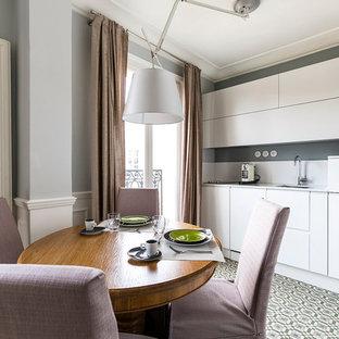 Idées déco pour une cuisine américaine linéaire contemporaine avec des portes de placard blanches, une crédence blanche, un placard à porte plane et aucun îlot.