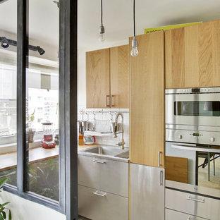 Cette image montre une cuisine design fermée avec un évier posé, un placard à porte plane, une façade en inox, un plan de travail en bois, une crédence blanche, une crédence en carrelage métro, un électroménager en acier inoxydable et aucun îlot.