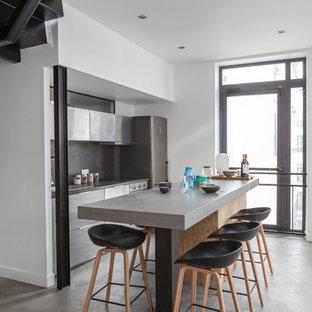 Ejemplo de cocina de galera, actual, de tamaño medio, abierta, con armarios con paneles lisos, puertas de armario en acero inoxidable, salpicadero verde, suelo de cemento y una isla