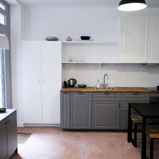 パリの中くらいのトランジショナルスタイルのおしゃれなキッチン (アンダーカウンターシンク、インセット扉のキャビネット、グレーのキャビネット、木材カウンター、白いキッチンパネル、パネルと同色の調理設備、テラコッタタイルの床、赤い床、ベージュのキッチンカウンター、セラミックタイルのキッチンパネル) の写真