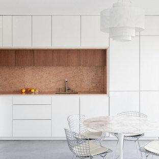 Diseño de cocina comedor en L, contemporánea, grande, con fregadero integrado, armarios con rebordes decorativos, puertas de armario blancas, encimera de mármol, salpicadero rosa, salpicadero de mármol, electrodomésticos con paneles, suelo de cemento, suelo gris y encimeras rosas