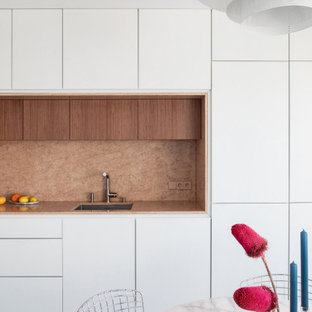 Photo of a large contemporary l-shaped eat-in kitchen in Paris with an integrated sink, beaded inset cabinets, white cabinets, marble benchtops, pink splashback, marble splashback, panelled appliances, concrete floors, grey floor and pink benchtop.