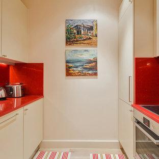 Foto på ett avskilt, mellanstort funkis röd parallellkök, med luckor med profilerade fronter, beige skåp, bänkskiva i kvarts, rött stänkskydd, stänkskydd i kalk, rostfria vitvaror, ljust trägolv och brunt golv