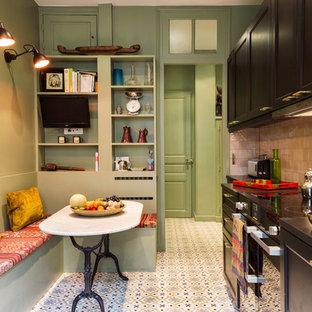 Cette photo montre une cuisine américaine linéaire chic avec un placard avec porte à panneau encastré, des portes de placard noires, une crédence beige, une crédence en mosaïque, un électroménager noir, aucun îlot, un sol multicolore et un plan de travail noir.