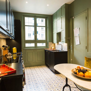 Photo of a large industrial single-wall eat-in kitchen in Paris with an undermount sink, cement tiles, recessed-panel cabinets, black cabinets, beige splashback, mosaic tile splashback, black appliances, no island, pink floor and black benchtop.