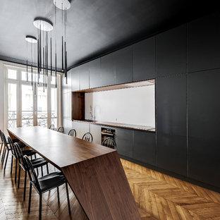 Inspiration pour une grande cuisine linéaire design avec un évier encastré, un placard à porte plane, des portes de placard noires, un plan de travail en bois, une crédence blanche, un sol en bois brun, un plan de travail marron, un électroménager noir et un sol marron.