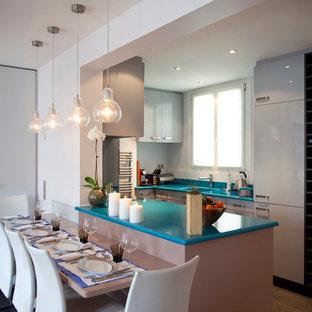 Aménagement d'une cuisine américaine parallèle contemporaine de taille moyenne avec des portes de placard blanches et une péninsule.