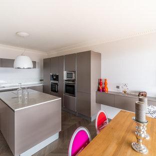 Cette image montre une grande cuisine ouverte linéaire design avec une crédence blanche, un sol en bois clair, un îlot central, un évier intégré, un placard sans porte, un plan de travail en quartz et un électroménager encastrable.