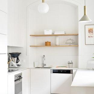 Idées déco pour une cuisine ouverte contemporaine en U de taille moyenne avec un évier intégré, des portes de placard blanches, un plan de travail en surface solide, une crédence blanche, un électroménager encastrable, un sol en bois clair et un plan de travail blanc.