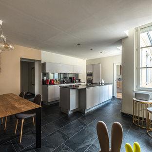 Réalisation d'une cuisine parallèle design avec un placard à porte plane, des portes de placard grises, un électroménager en acier inoxydable, un îlot central, un sol noir et un plan de travail gris.