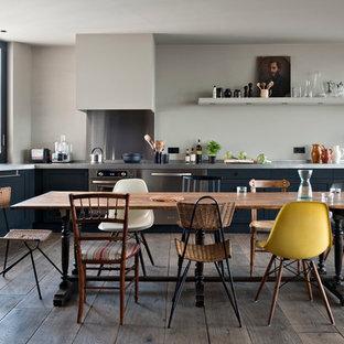 Inspiration pour une grand cuisine ouverte urbaine en L avec des portes de placard noires, un plan de travail en inox, une crédence métallisée, une crédence en dalle métallique, un électroménager en acier inoxydable, un sol en bois foncé et aucun îlot.