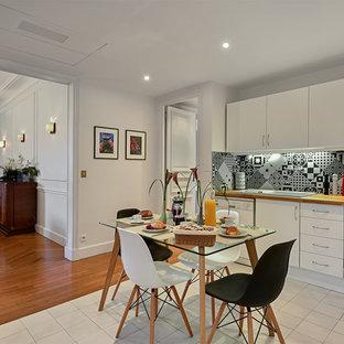 Cette image montre une grand cuisine ouverte design en L avec un placard à porte affleurante, des portes de placard blanches, un plan de travail en bois, une crédence en carreau de ciment, un électroménager blanc, un sol en carrelage de céramique, un évier posé et une crédence multicolore.