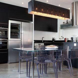 Cette image montre une grande cuisine américaine design en U avec des portes de placard noires et une péninsule.