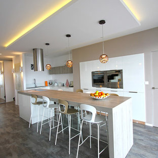 This is an example of a mid-sized contemporary u-shaped eat-in kitchen in Lyon with an undermount sink, white cabinets, laminate benchtops, white splashback, stainless steel appliances, laminate floors, with island, beige benchtop, flat-panel cabinets, glass sheet splashback and grey floor.