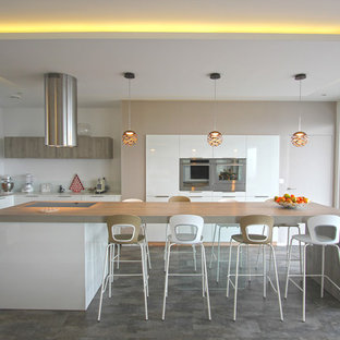 Photo of a mid-sized contemporary u-shaped eat-in kitchen in Lyon with white cabinets, white splashback, glass sheet splashback, stainless steel appliances, with island, flat-panel cabinets, an undermount sink, laminate benchtops, laminate floors, beige benchtop and grey floor.