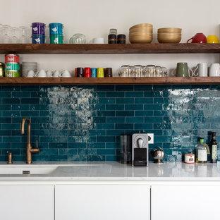 Bild på ett mellanstort 50 tals vit linjärt vitt kök med öppen planlösning, med vita skåp, marmorbänkskiva, blått stänkskydd, stänkskydd i keramik, cementgolv, en köksö och blått golv
