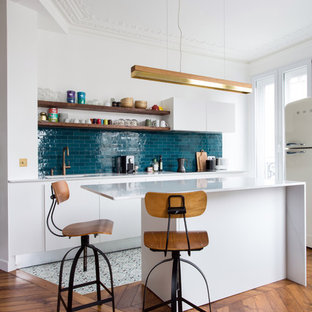 Inspiration for a mid-sized contemporary galley open plan kitchen in Paris with marble benchtops, blue splashback, ceramic splashback, cement tiles, with island, white benchtop, flat-panel cabinets, white cabinets, white appliances and multi-coloured floor.