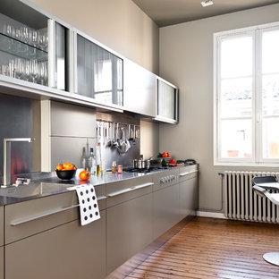 Ispirazione per una cucina parallela design chiusa e di medie dimensioni con lavello integrato, ante lisce, ante grigie, top in acciaio inossidabile, paraspruzzi a effetto metallico, pavimento in legno massello medio e nessuna isola