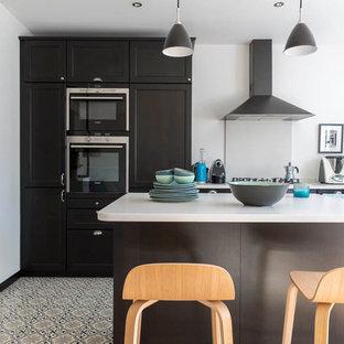 Inspiration pour une cuisine ouverte design en L de taille moyenne avec des portes de placard noires, un plan de travail en surface solide, un sol en carrelage de céramique, un îlot central, une crédence blanche, un évier encastré, un électroménager encastrable et un sol multicolore.