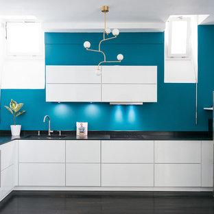 Offene, Mittelgroße Moderne Küche in L-Form mit integriertem Waschbecken, weißen Schränken, Granit-Arbeitsplatte, Küchenrückwand in Blau, schwarzen Elektrogeräten, gebeiztem Holzboden und schwarzem Boden in Paris