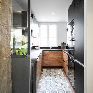 Moderne Küche in U-Form mit flächenbündigen Schrankfronten, schwarzen Schränken, Halbinsel und blauem Boden in Paris
