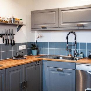 Idée de décoration pour une cuisine tradition en L fermée et de taille moyenne avec un évier 2 bacs, un placard avec porte à panneau surélevé, des portes de placard grises, un plan de travail en bois, une crédence bleue, un électroménager en acier inoxydable et aucun îlot.