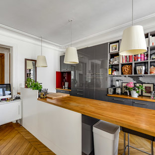 Idées déco pour une cuisine ouverte parallèle contemporaine avec un placard à porte plane, des portes de placard grises, un plan de travail en bois, une crédence multicolore, un sol en bois brun, un îlot central et un sol jaune.