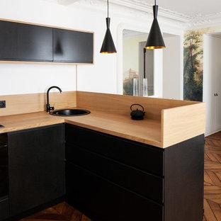 パリの中サイズのコンテンポラリースタイルのおしゃれなキッチン (アンダーカウンターシンク、フラットパネル扉のキャビネット、黒いキャビネット、木材カウンター、ベージュキッチンパネル、木材のキッチンパネル、無垢フローリング、アイランドなし、茶色い床) の写真