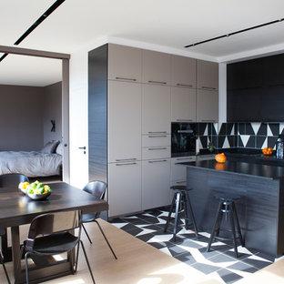 Свежая идея для дизайна: угловая кухня среднего размера в скандинавском стиле с обеденным столом, светлым паркетным полом, коричневым полом, врезной раковиной, фасадами с декоративным кантом, черными фасадами, столешницей из кварцита, разноцветным фартуком, фартуком из керамической плитки, черной техникой, островом и черной столешницей - отличное фото интерьера