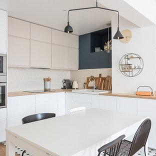 Exemple d'une grand cuisine ouverte scandinave en L avec un évier 1 bac, un placard à porte affleurante, des portes de placard blanches, un plan de travail en bois, une crédence beige, une crédence en carreau de terre cuite, un électroménager en acier inoxydable, un sol en carrelage de porcelaine, aucun îlot, un sol multicolore et un plan de travail beige.