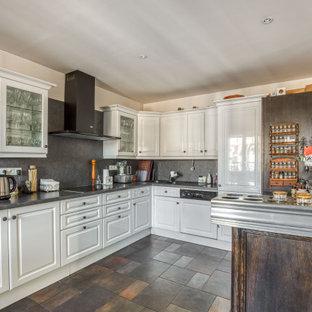 Aménagement d'une cuisine classique en U fermée avec un placard avec porte à panneau surélevé, des portes de placard blanches, un électroménager encastrable, une péninsule, un sol gris et un plan de travail gris.