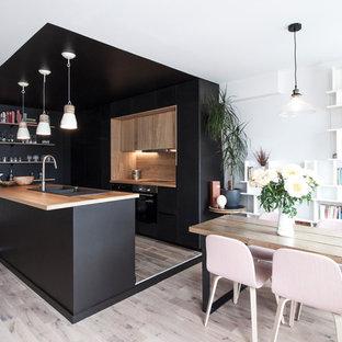 Diseño de cocina de galera, escandinava, de tamaño medio, abierta, con fregadero de doble seno, puertas de armario negras, encimera de madera, electrodomésticos negros, suelo de madera clara, una isla y salpicadero marrón