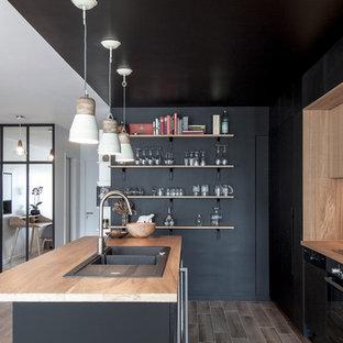 Aménagement d'une cuisine ouverte parallèle scandinave de taille moyenne avec un évier 2 bacs, des portes de placard noires, un plan de travail en bois, un électroménager noir, un îlot central, une crédence marron et un sol en carrelage de céramique.