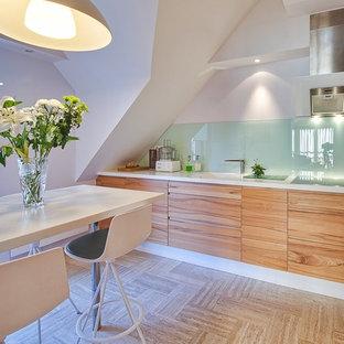 Idées déco pour une cuisine américaine moderne en L de taille moyenne avec des portes de placard en bois brun, une crédence verte, une crédence en feuille de verre et aucun îlot.