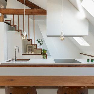 Réalisation d'une cuisine ouverte nordique de taille moyenne avec un évier 1 bac, un placard à porte plane, des portes de placard blanches, un îlot central et un plan de travail blanc.