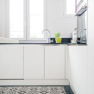 Cette photo montre une cuisine tendance en L fermée et de taille moyenne avec un placard à porte plane, des portes de placard blanches et aucun îlot.