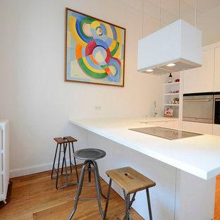 Idée de décoration pour une cuisine américaine design en L de taille moyenne avec des portes de placard blanches, un électroménager encastrable et une péninsule.