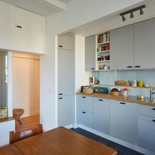 パリのエクレクティックスタイルのおしゃれなキッチン (グレーのキャビネット、木材カウンター、セラミックタイルのキッチンパネル、セラミックタイルの床、黒い床) の写真