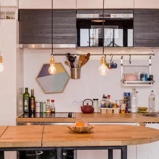 Small industrial single-wall eat-in kitchen in Paris with wood benchtops, panelled appliances, concrete floors, black floor, an integrated sink, beaded inset cabinets, white cabinets and white splashback.