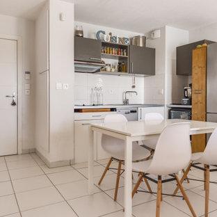 Idée de décoration pour une petit cuisine américaine design en L avec un placard à porte plane, des portes de placard grises, un électroménager en acier inoxydable, un îlot central, un sol blanc et un plan de travail gris.